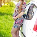 Happy smiling pregnant driver woman is standing near car near the road with green grass, summer time